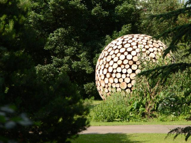 oeuvre d'art et boule sphérique en bois se trouvant dans le jardin botanique de Meyrin